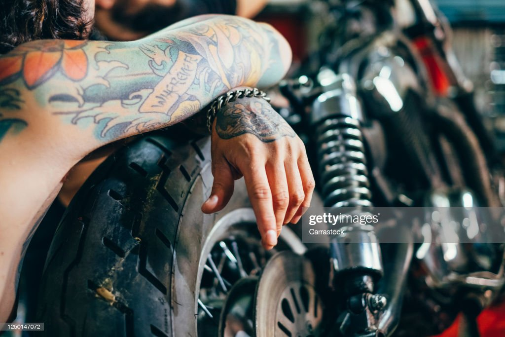 Man Biker With Tattoos Poses Together His Motorcycle In Workshop High Res Stock Photo Getty Images