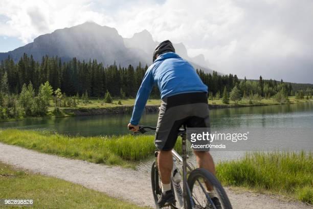 Bicicletas de hombre a lo largo de la ruta de acceso al lago en las montañas cuando se acerca la tormenta