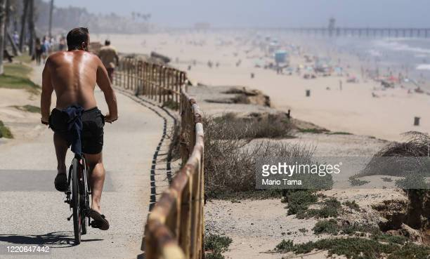 A man bikes on a bike path as people gather on Huntington Beach which remains open amid the coronavirus pandemic on April 23 2020 in Huntington Beach...