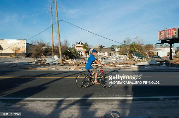 A man bikes past a destroyed gas station near Port Saint Joe Florida on October 12 two days after hurricane Michael hit the area Rescue teams using...
