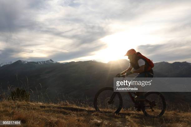 man bikes uphill in backlit grasses and mountains. - cross country cycling stock pictures, royalty-free photos & images