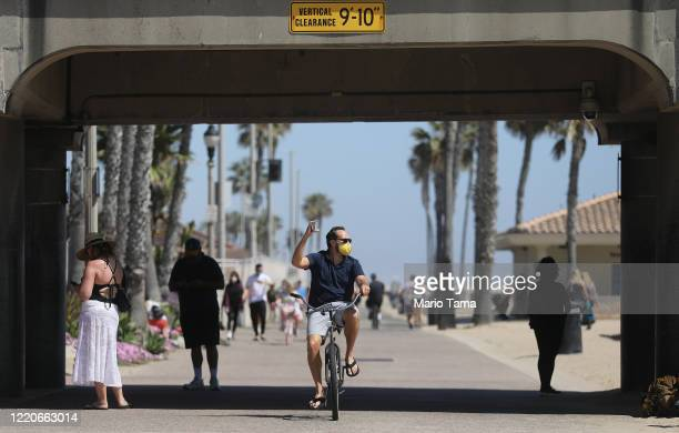 A man bikes while wearing a face mask along Huntington Beach which remains open amid the coronavirus pandemic on April 23 2020 in Huntington Beach...