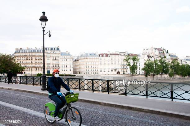 man biking in paris, with a mask during epidemic covid 19. - river seine stock pictures, royalty-free photos & images