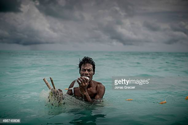 A man bites to kill a fish he caught in a fishing net Fishing has been the main diet of Kiribati but in recent years the fish population has...