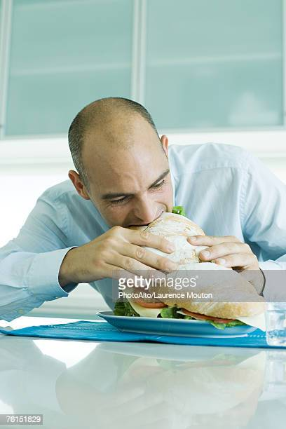 Man biting into large sandwich