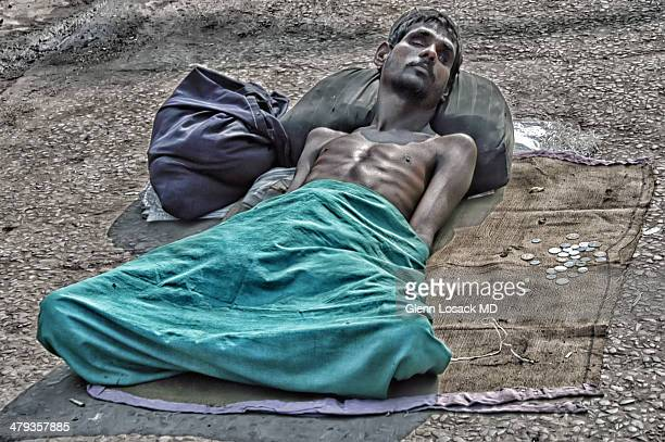 Man blinded deformed half hidden under a green material lays on the ground begging Delhi INDIA