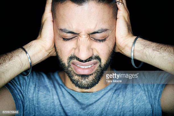man blocking ears looking stressed - bangle stock pictures, royalty-free photos & images