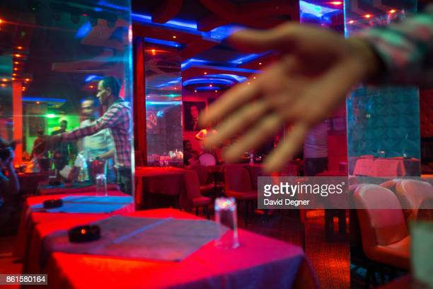 A man blocks the camera at a night club of belly dancers on Haram Street on May 17 2017 in Cairo Egypt The street is famous for its night clubs that...