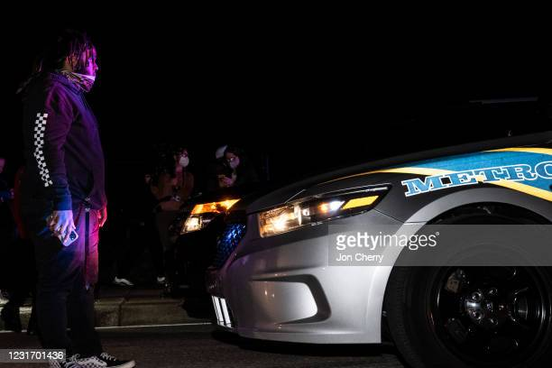 Man blocks the road while a police cruiser waits after the Breonna Taylor memorial events on March 13, 2021 in Louisville, Kentucky. Today marks the...