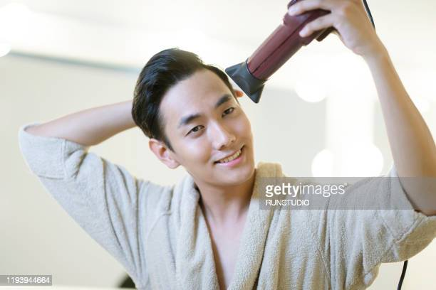 man blow drying hair - blow drying hair stock pictures, royalty-free photos & images