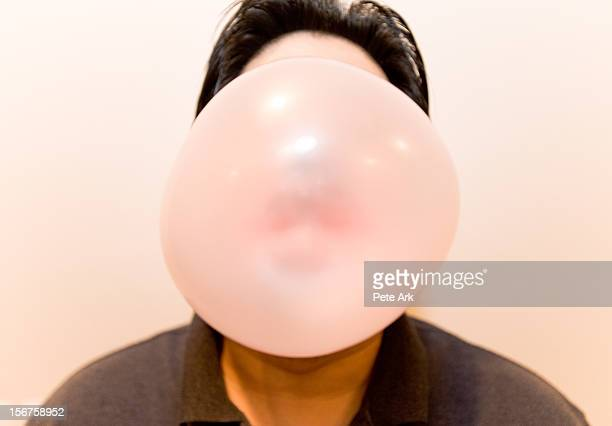 Man blowing a big bubble with bubble gum.