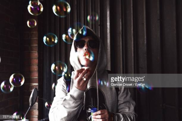 Man Blowing Bubbles While Standing Against Wall