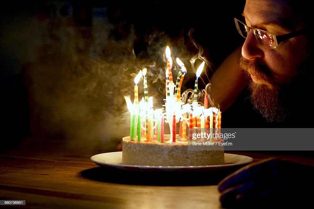 Man blowing candles on birthday cake stock photo getty images man blowing candles on birthday cake stock photo sciox Image collections