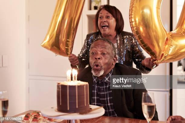 man blowing candles on cake during birthday party - 70 79 jaar stockfoto's en -beelden