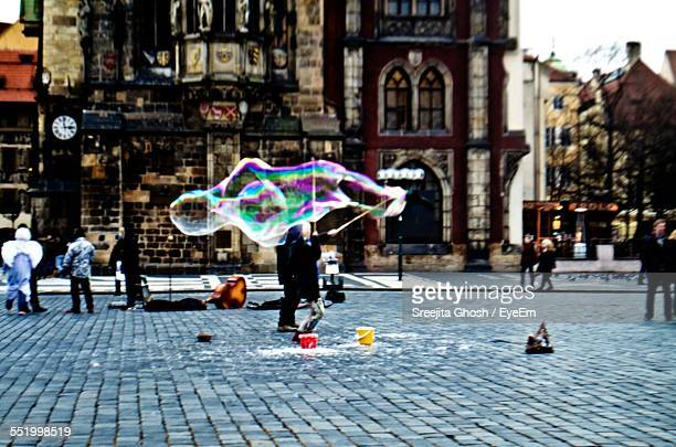 Man Blowing Colorful Oversized Soap Bubbles