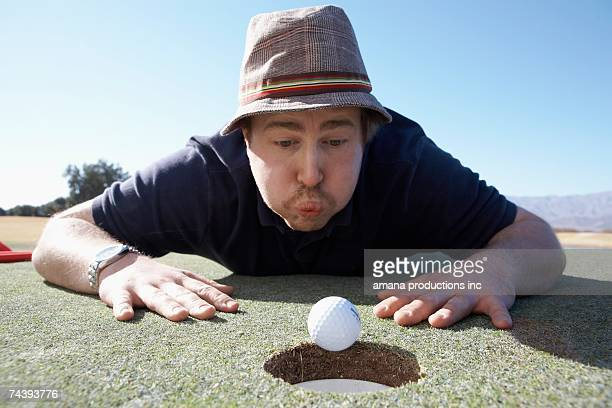 Man blowing golf ball to hole