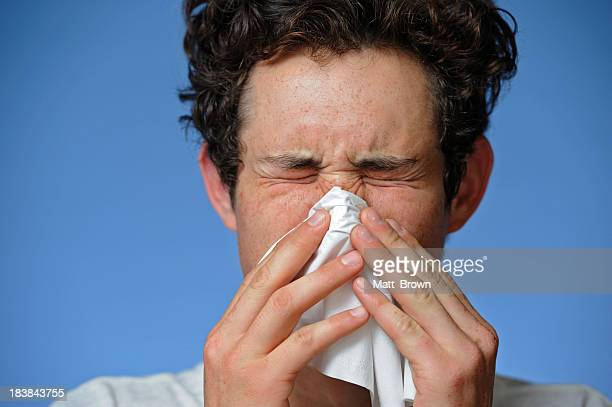 A man blowing his nose into a tissue