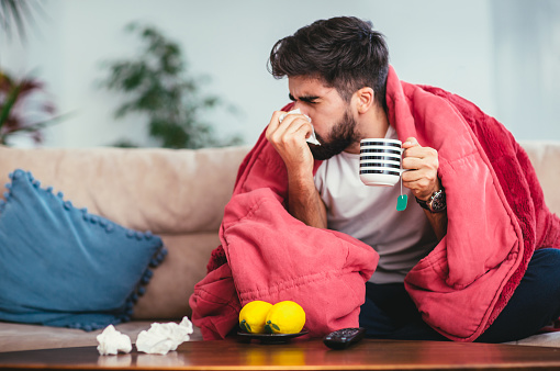 Man blowing his nose while lying sick in bed 924698666