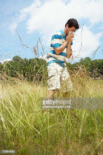 man blowing nose in field (low angle view) - tree man syndrome stock photos and pictures