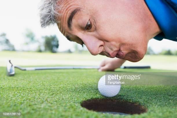 Hombre que sopla sobre la pelota de golf