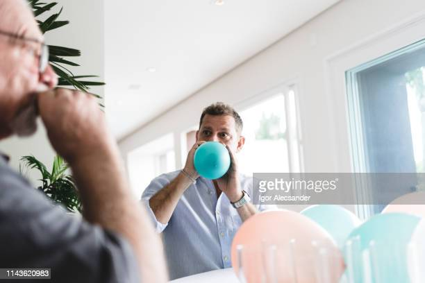 man blowing party balloon - inflating stock pictures, royalty-free photos & images