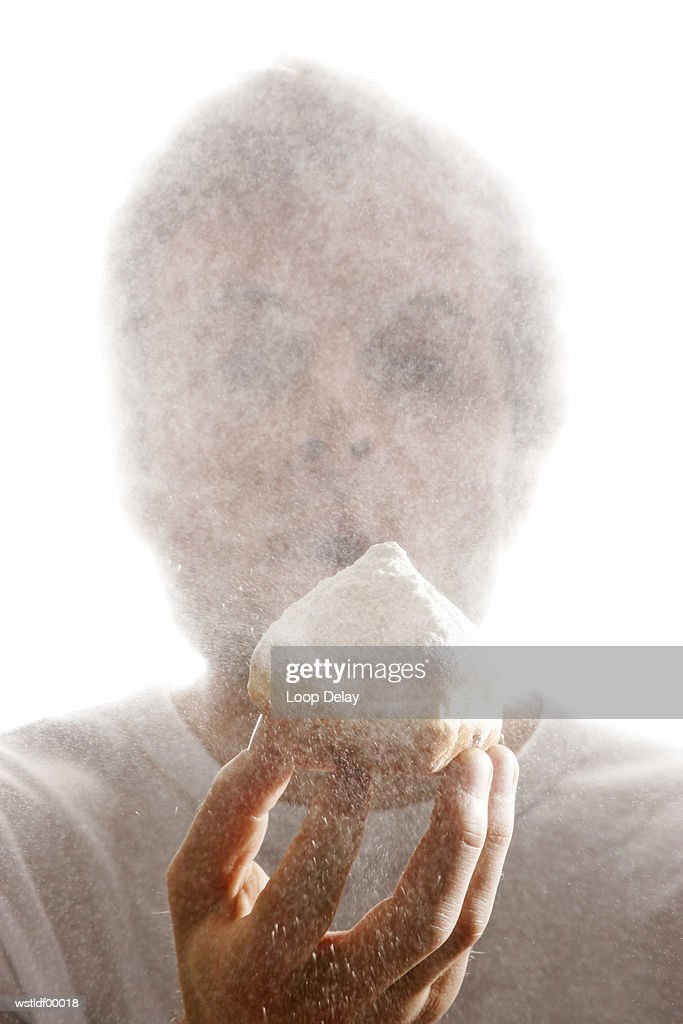 Man, blowing sugar powder from a Krapfen, typical German doughnut : Stock Photo