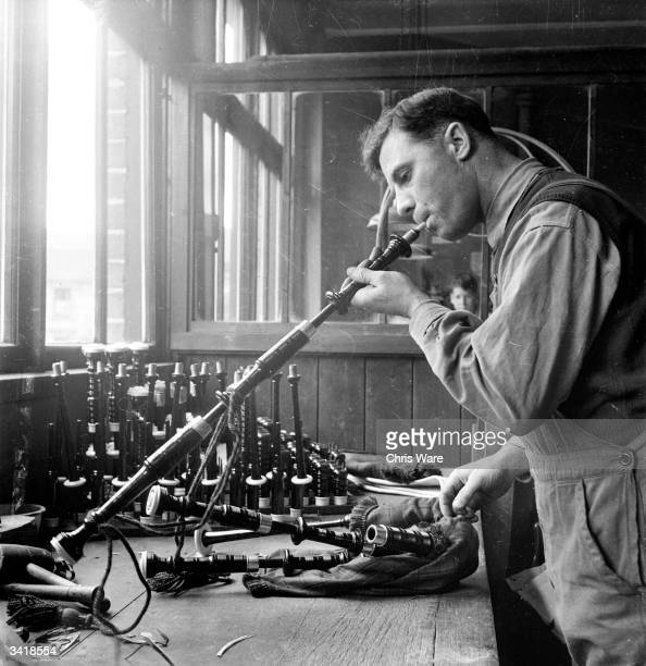 A man blowing through a chanter to test it for adequate clearance at a bagpipe workshop in Glasgow On the right is a complete set of bagpipes...