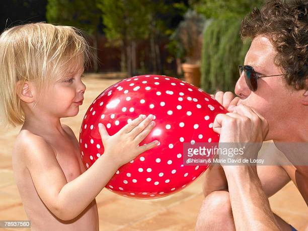 man blowing up a balloon for a young girl. - saint ferme stock pictures, royalty-free photos & images