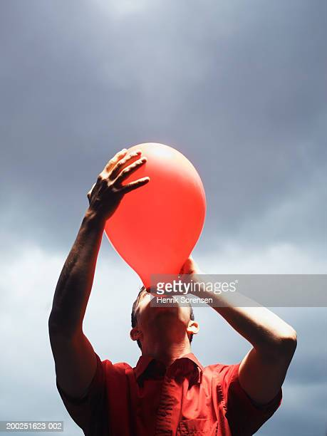 man blowing up red balloon - inflating stock pictures, royalty-free photos & images