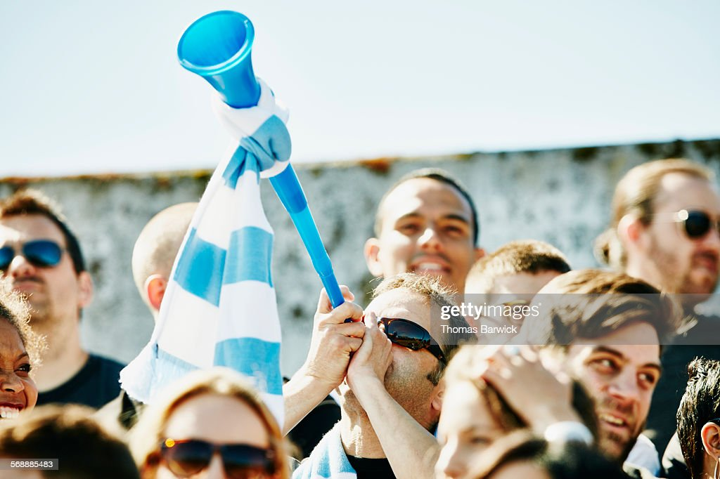 Man blowing vuvuzela in crowd during soccer match : Stock Photo