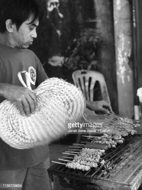man blowing wind from hand fan while cooking food on barbecue - nadal stock pictures, royalty-free photos & images
