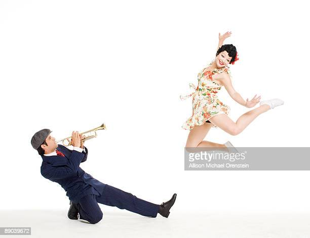man blowing woman away with trumpet