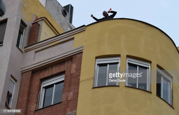 Man blows a horn from his rooftop in honour of Spanish healthcare workers on April 04, 2020 in Madrid, Spain. Spain ordered all non-essential workers...
