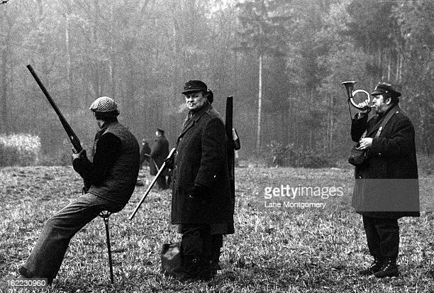 A man blows on a bugle to signal a shot bird while with a hunting party in Czechoslovakia 1995