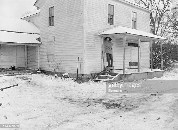 Man boarding up the former home of serial killer Ed Gein in Plainfield in Wisconsin in 1957. Gein murdered women in his town and robbed many graves...