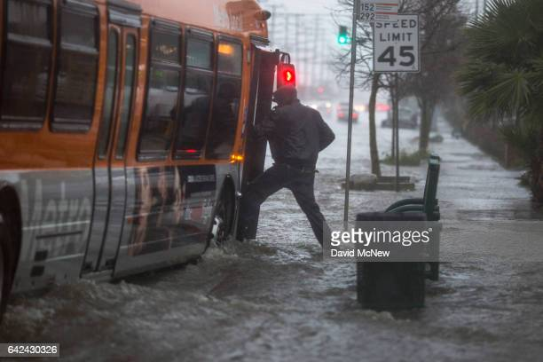 A man boards a bus on a flooded street as a powerful storm moves across Southern California on February 17 2017 near Sun Valley California After...