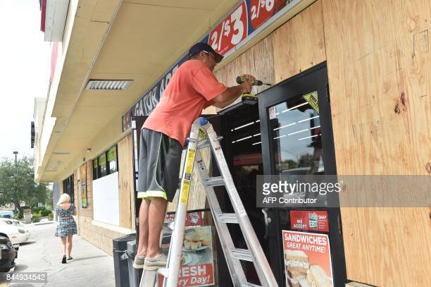 A man boards up a convenient store in Port Charlotte Florida on September 9 2017 Hurricane Irma weakened slightly to a Category 4 storm early...