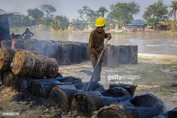 A man boils bitumen which is used for the production of tarmac for the road construction on April 11 2016 in Khulna Bangladesh