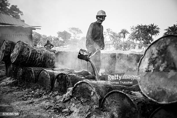 Image has been converted to black and white KHULNA BANGLADESH APRIL 11 A man boils bitumen which is used for the production of tarmac for the road...
