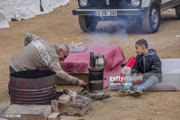 A man boils water for tea near tents built by Turkish Red Crescent and Turkeyâs Disaster and Emergency Management Authority for those affected by the...