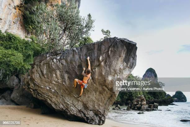 a man boulders above a sandy beach - railay strand stock-fotos und bilder