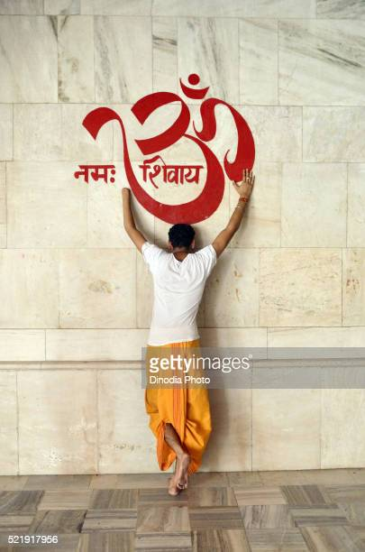 Man bowing to OM on temple wall at Jodhpur, rajasthan, India
