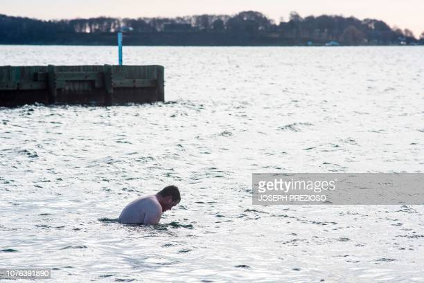 A man bows his head in the water during the annual L Street Brownies New Year's Day Plunge at the Curley Community Center in South Boston...