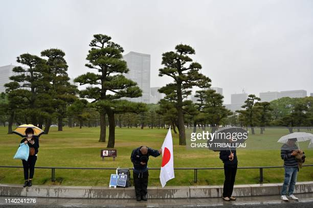 A man bows while holding a Japan national flag as people gather outside the Imperial Palace where the abdication ceremony for Japan's Emperor Akihito...
