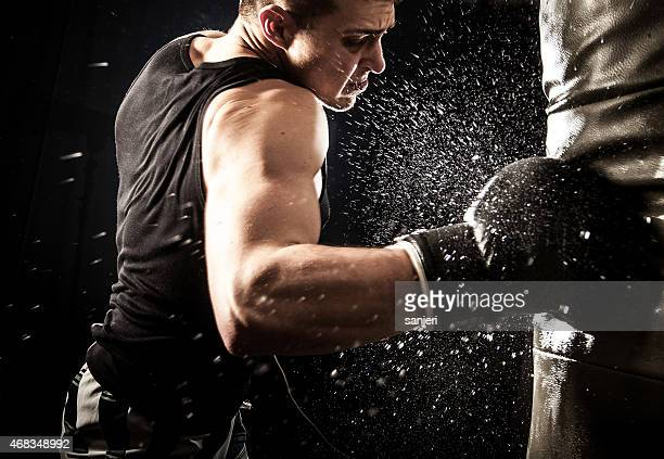 A man boxing hard while water flies