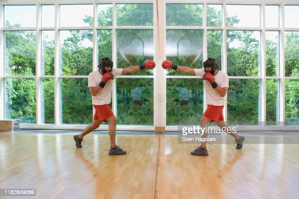a man boxing his mirrored reflection - boxing shorts stock pictures, royalty-free photos & images
