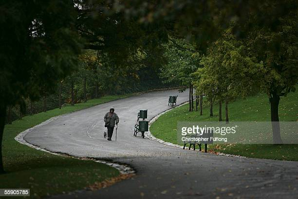 A man braves the autumn rain as he walks his dog in a park on October 10 2005 in Glasgow Scotland Seasonal affective disorder or winter depression is...