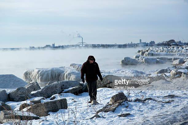 A man braves the cold and walks along the shore of Lake Michigan as temperatures remain in the negative digits on January 7 2014 in Milwaukee...