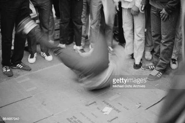 Man breakdancing on cardboard on a street in New York City, circa 1984.