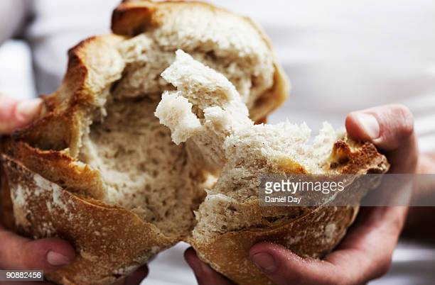 man breaking bread  - loaf of bread stock pictures, royalty-free photos & images